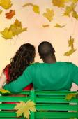 Black man and asian woman under leaf fall from — Stock Photo