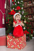 Child dressed as Santa in box with gift bag — Stock Photo