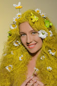 Woman with yellow hair, flowers, and bees in them — Stock Photo