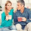 Happy Christmas couple drinking tea on the home sofa with tree o — Stock Photo #52307369
