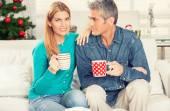 Gelukkige Kerstmis paar het drinken van thee op de home Bank met tree o — Stockfoto