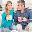 Happy Christmas couple drinking tea on the home sofa with tree o — Stock Photo #52365609
