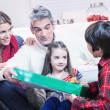 Family Scene. Parents With Children Opening Presents In Front Of — Stock Photo #52366189