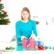 Woman in her living room opening Christmas gift — Stockfoto