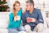 Happy Christmas couple drinking tea on the home sofa with tree o — Stock Photo