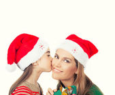 Family, Christmas concept. Adorable child kisses her mother and — Stock Photo