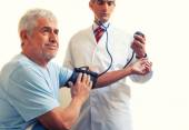 Young doctor measuring blood pressure to a senior man. Isolated — Stock Photo