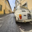 Постер, плакат: Old cinquecento parked in a narrow city street