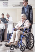 Woman on wheelchair with her caregiver. — Stock Photo