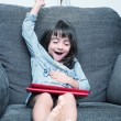 Girl smiling while playing with tablet — Stock Photo #60181023