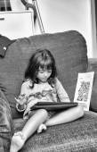 Girl smiling while playing with tablet — Stockfoto