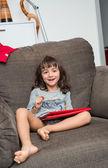 Flickan ler medan du spelar med tablett — Stockfoto
