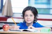 Dziecko w szkole pisze w swojej książce z jabłkiem na biurku — Zdjęcie stockowe