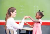 Happy teacher and afroamerican elementary student congratulating — Stock Photo