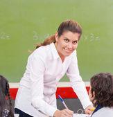 Happy female teacher checking students homework at school — Stock Photo
