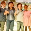 Happy mixed race primary schoolmates standing with thumbs up — Stock Photo #63843431