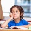 Primary school kid thinking about answer sitting at his desk — 图库照片 #65013649