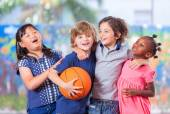 Happy children embracing while playing basketball. Primary schoo — Stock Photo