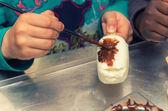 Hands of primary school children putting chocolate on ice cream — Stock Photo
