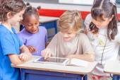 Schoolchildren playing with tablet — Stock Photo