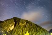 Star trails in sky above mountains — Stock Photo
