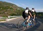 Cyclists on a Tandem bicycle riding uphill on a mountain roadway — Stock Photo