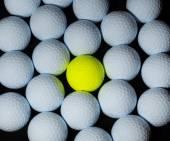 Golf balls. Single yellow ball mixed within many white balls. — Stock Photo