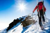 Climberr walking up along a steep snowy ridge with the skis in t — Stock Photo