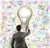 Businessmen draws light bulb — Photo