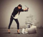 Businesswoman attacking computers and laptops — Stock Photo