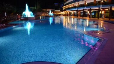 Panning up of the swimming pool and building of luxury hotel in night illumination, Antalya, Turkey — Stock Video
