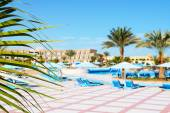 The frond of palm and swimming pool at luxury hotel, Hurghada, E — Stock Photo