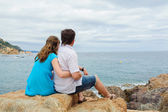 Young couple sit near the sea — Stock Photo