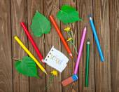 Colored pencils and eraser on a wooden background — Stock Photo