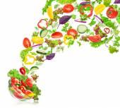 Mélange de légumes frais tomber dans un bol de salade sur un isolat — Photo