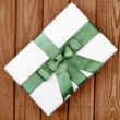 Gift box with bow on wooden background — Stock Photo #54043355