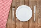 White plate and fork on old wooden table with red cloth — Stock Photo