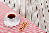 Cup of coffee on a fabric on a wooden table — Stock Photo