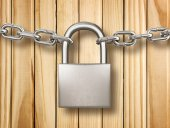 Locked padlock with silver chains isolated on wood background. S — Stockfoto
