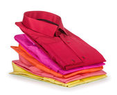 Stack of colored shirt on a white background — Stock Photo