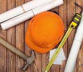 Hammer, folding ruler, blueprint and yellow safety helmet on woo — Stock Photo