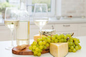 Various sorts of cheese, grapes and two glasses of the white win — Stockfoto