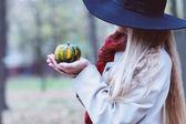Portrait of the beautiful woman wearing black hat holding little — Stockfoto