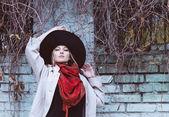 Beautiful woman wearing black hat in the autumn day — Stockfoto