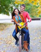 Happy couple with bicycle in autumn park — Stok fotoğraf