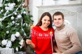 Young couple sitting by Cristmas tree — Stock Photo