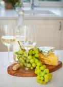 Various sorts of cheese, grapes and two glasses of the white win — Stock Photo
