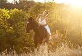 Beautiful woman on a horse — Stock Photo