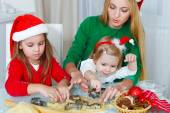 Two little girls with mother baking Christmas cookies — Stock Photo