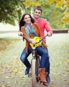 Happy couple with bicycle in autumn park — Stock Photo